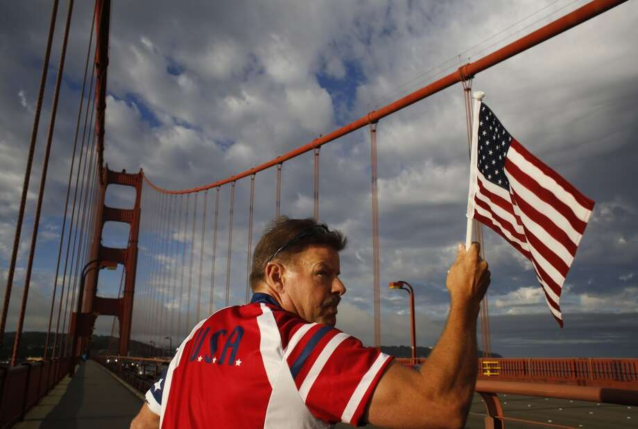 "Known as the ""Flag Man,"" Rob Peterson, 52, looks back after a motorist honks at while he walks the Golden Gate bridge in San Francisco, Calif. He has been walking the bridge on and off since 2002 and estimates he's done the morning trek at least 1,000 times. Photo: Mike Kepka"