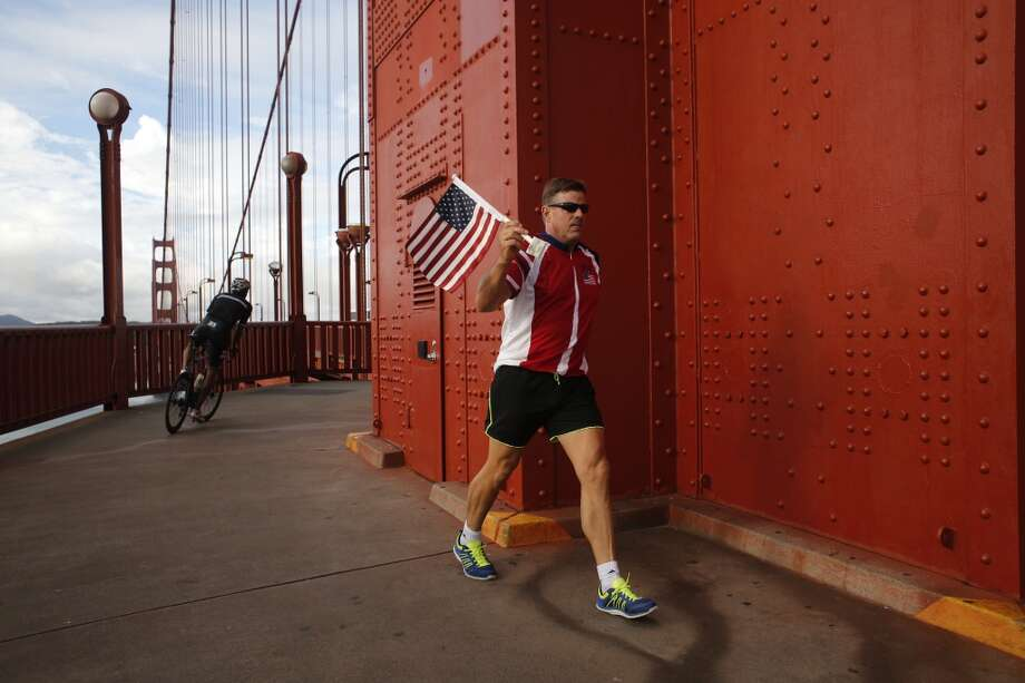 "Known as the ""Flag Man,"" Rob Peterson, 52, passes the north tower on one of his daily Golden Gate bridge walks in San Francisco, Calif  ""The flag to me represents our country and what it stands for,"" said Peterson. ""It also brings to mind the people that have paid the ultimate price for our freedom."""