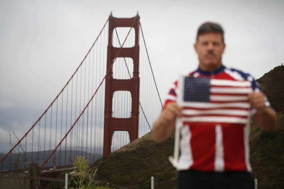 "Holding his second American flag after the first wore out from years of use,  ""Flag Man"" Rob Peterson, 52, prepares to walk the Golden Gate bridge. Photo: Mike Kepka"