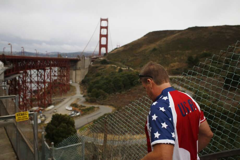 "Headed to a path under the north side of the Golden Gate Bridge,  ""Flag Man"" Rob Peterson, 52, starts his morning walk over the bridge. Photo: Mike Kepka"