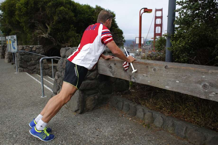 "Known as the ""Flag Man,"" Rob Peterson, 52, stretches and does a series of pushups before walking the Golden Gate Bridge. Photo: Mike Kepka"