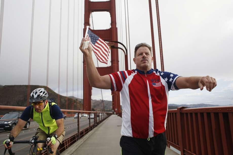 "A cyclist rides past ""Flag Man,"" Rob Peterson, 52, as he walks the Golden Gate bridge in San Francisco, Calif Photo: Mike Kepka"