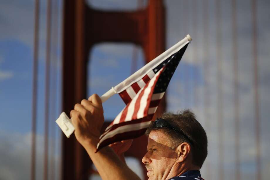 """Flag Man,"" Rob Peterson, 52, takes a quick moment to look as his surroundings as he walks the Golden Gate bridge in San Francisco, Calif. Photo: Mike Kepka"