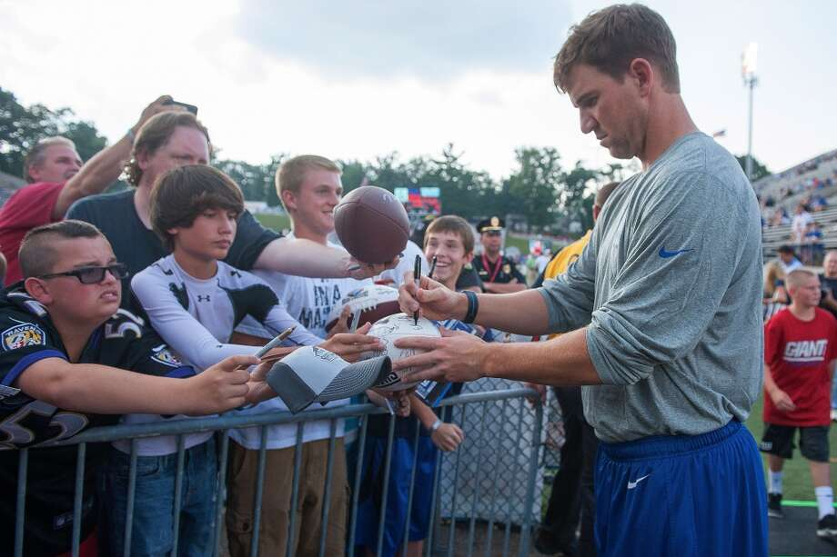 Quarterback Eli Manning #10 of the New York Giants signs autographs prior to a game against the Buffalo Bills at the 2014 NFL Hall of Fame Game. Photo: Jason Miller, Getty Images