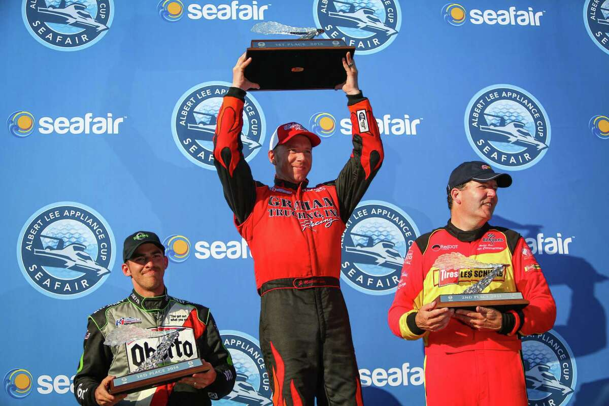 From left, Jimmy Shane of the Oberto Unlimited Hydroplane, J. Michael Kelly of the Graham Trucking boat and Jon Zimmerman of the Les Schwab Tires - Team Red Dot boat hoist their trophies after Kelly won the Albert Lee Appliances Seafair Cup during Seafair on Sunday, August 3, 2014.