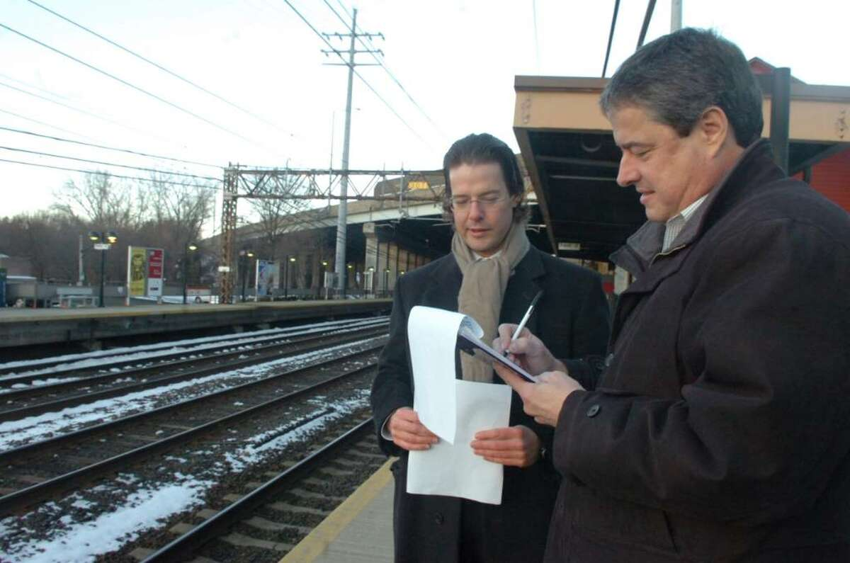 Wayne Jervis, left, convinces Victor Coutinho, right, to signs a petition to keep the cell tower further away from Cos Cob schools and residences at the Cos Cob railroad station, on Thursday, February 18, 2010.