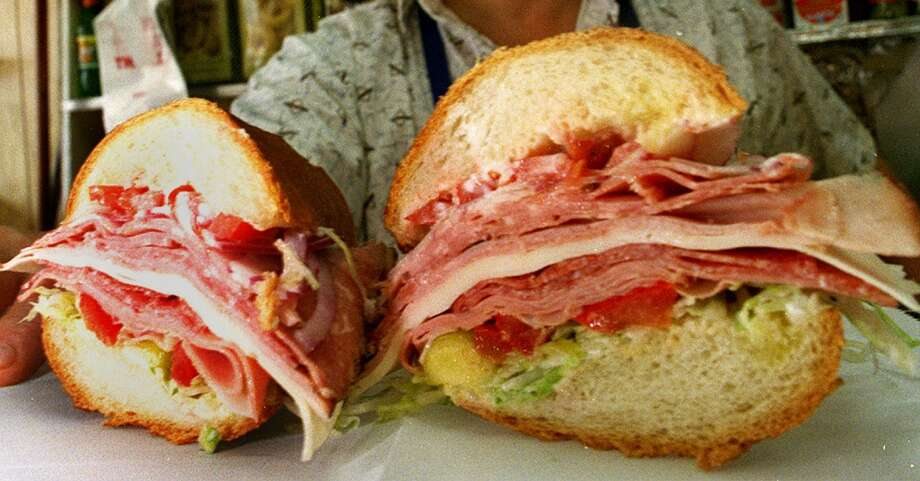 A hard roll sandwich with the Italian works from the twins (Ricky and Robert) at Panelli Brothers. Pictured: Richard Panelli stands behind a freshly made Panelli's Combo sandwich at the Panelli Brothers Deli on Stockton Street. Submitted by SFGate user 'cityfreak.'