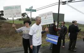 File - In this Feb. 10, 2014, file photo, Julie Graves, left, of Albany, Calif., and Chris Adams, second from left, of Berkeley, Calif., hold up signs in support of a beach access bill that Democratic state Sen. Jerry Hill introduced near Martin's Beach in Half Moon Bay, Calif. California's Coastal Commission is asking the public to document its use of Martin's Beach after billionaire landowner Vinod Khosla closed the only access road to it. (AP Photo/Eric Risberg, File)