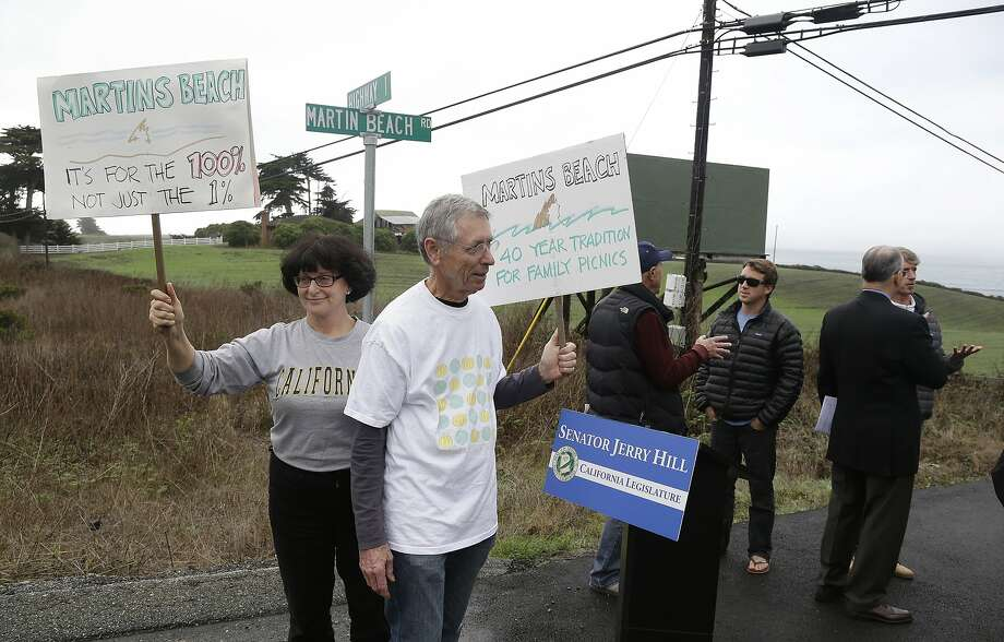 File - In this Feb. 10, 2014, file photo, Julie Graves, left, of Albany, Calif., and Chris Adams, second from left, of Berkeley, Calif., hold up signs in support of a beach access bill that Democratic state Sen. Jerry Hill introduced near Martin's Beach in Half Moon Bay, Calif. California's Coastal Commission is asking the public to document its use of Martin's Beach after billionaire landowner Vinod Khosla closed the only access road to it. (AP Photo/Eric Risberg, File) Photo: Eric Risberg, Associated Press