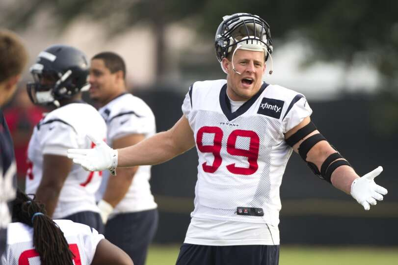 Texans defensive end J.J. Watt talks to a teammate before practice.