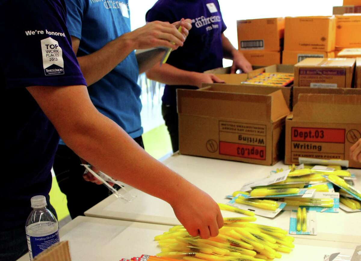 Teen volunteers and Cap Com staff gather school supplies to assemble backpacks for children in need Monday morning, Aug. 4, 2014, at Cap Com in Albany N.Y. (Selby Smith/Special to the Times Union)
