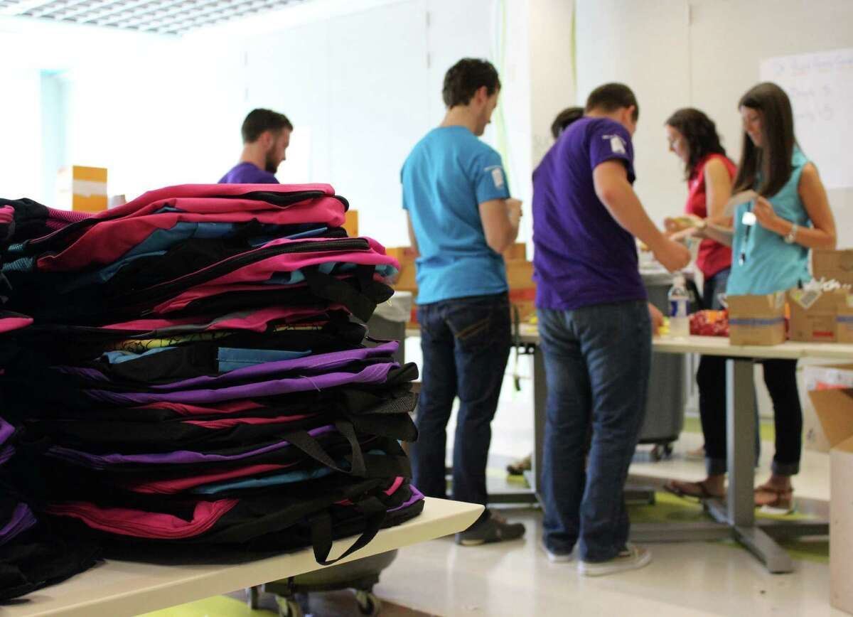 Teen volunteers and CCap Com staff gather school supplies to assemble backpacks for local children in need Monday morning, Aug. 4, 2014, in Albany N.Y. (Selby Smith/Special to the Times Union)