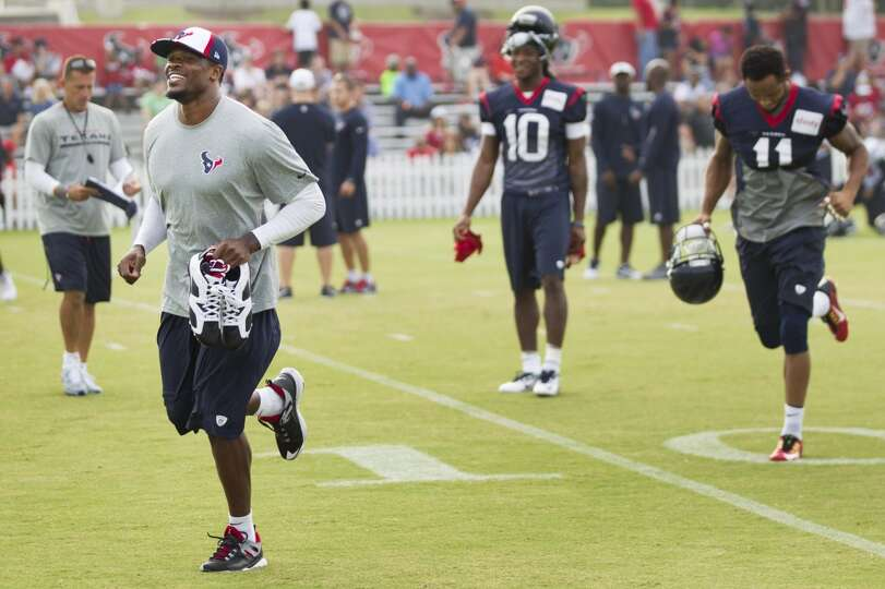 Texans wide receiver Andre Johnson, left, jogs onto the practice field.