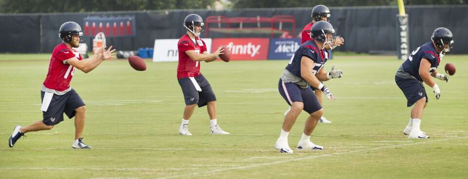 Texans quarterbacks Ryan Fitzpatrick (14), and Case Keenum (7) take a shotgun snap from Chris Myers