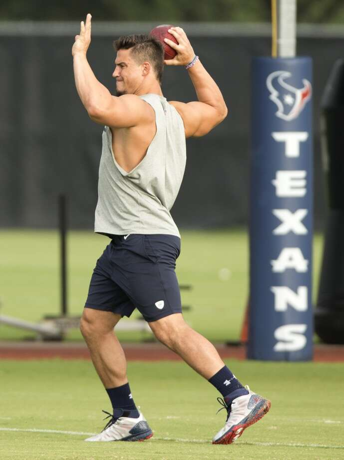 Inside linebacker Brian Cushing reaches back to throw a football. Cushing remains out of practice, recovering from a knee injury suffered last season. Photo: Brett Coomer, Houston Chronicle