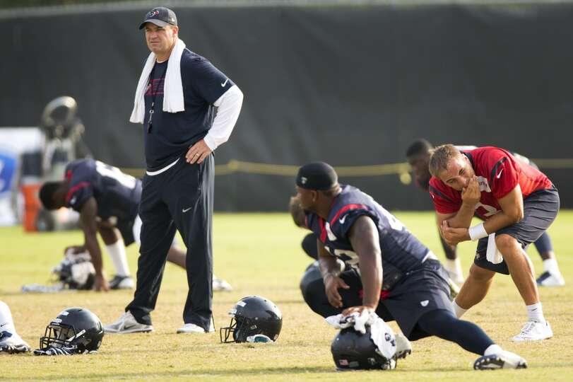 Texans head coach Bill O'Brien watches his players stretch.