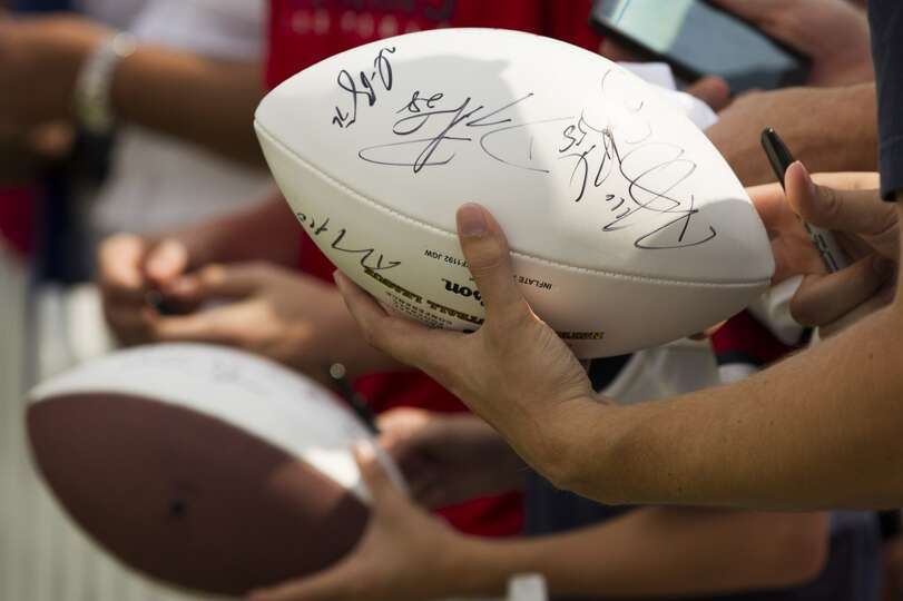 Texans fans hold autographed footballs.