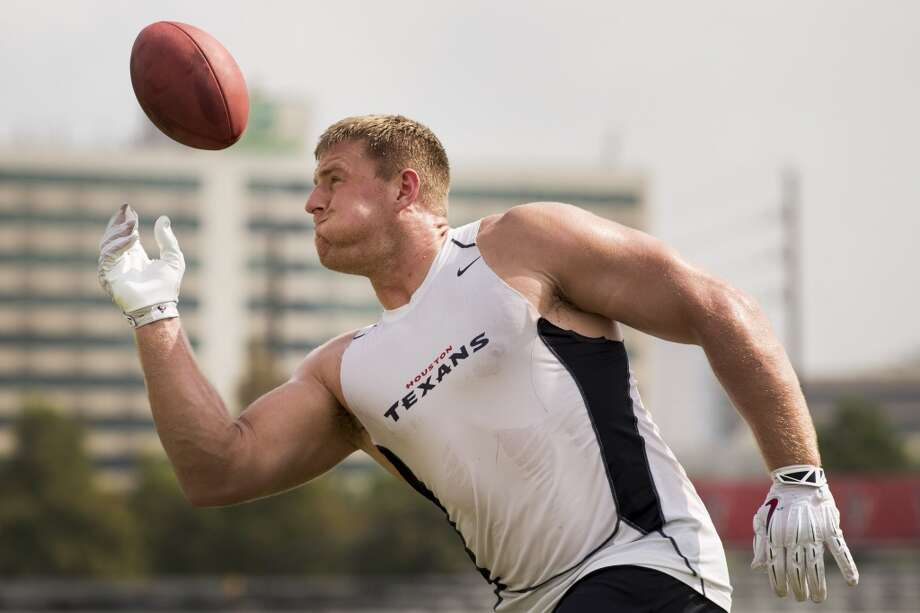 Defensive end J.J. Watt works on catching the football with one hand after practice. Photo: Brett Coomer, Houston Chronicle