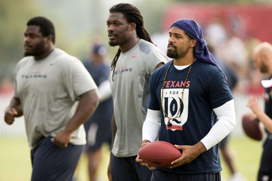 Texans defensive tackle Louis Nix III, left, linebacker Jadeveon Clowney (90) and running back Arian Foster (23) walk onto the practice field. All three players were out of uniform due to injury. Photo: Brett Coomer, Houston Chronicle
