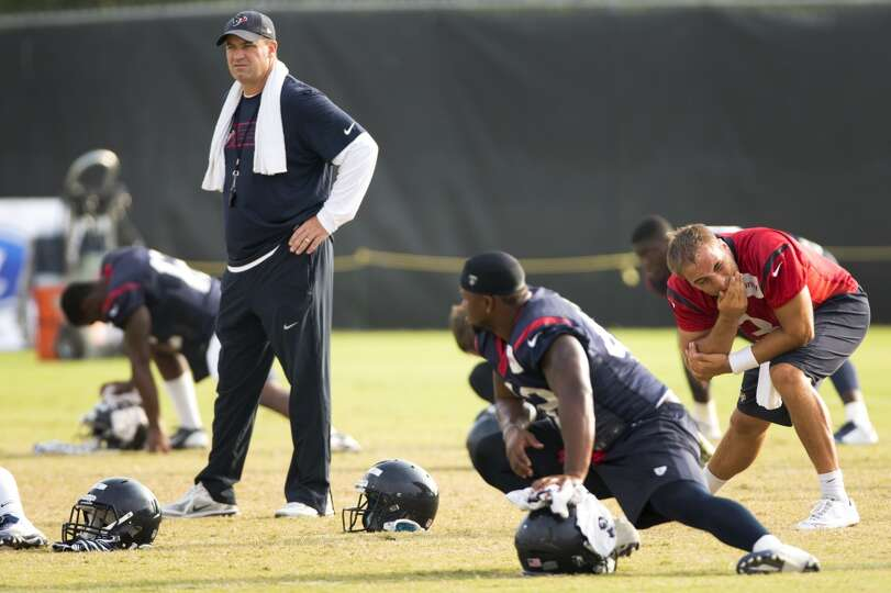 Texans head coach Bill O'Brien watches his players stretch.