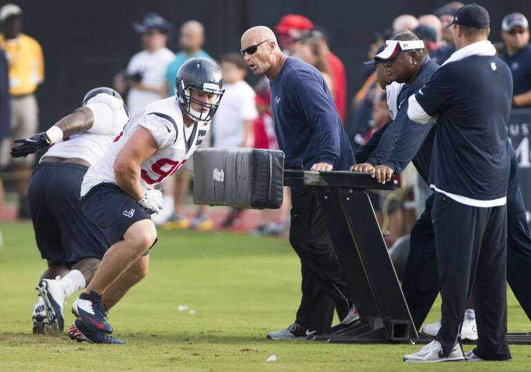 Texans defensive line coach Bill Kollar, right, runs J.J. Watt (99) through a drill as defensive coo