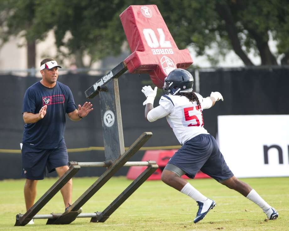 Assistant special teams coach Doug Coleman, left, stands on a blocking sled as it is hit by  outside linebacker Justin Tuggle (57). Photo: Brett Coomer, Houston Chronicle