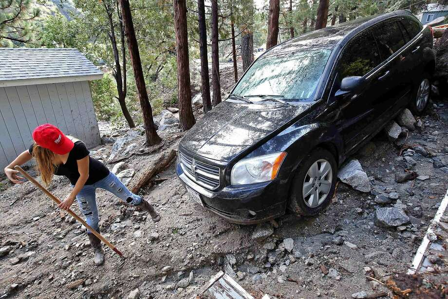 Jessica Gosney digs out her car after rocks and mud inundated her home in Forest Falls in the San Bernardino Mountains. Photo: Nick Ut, Associated Press