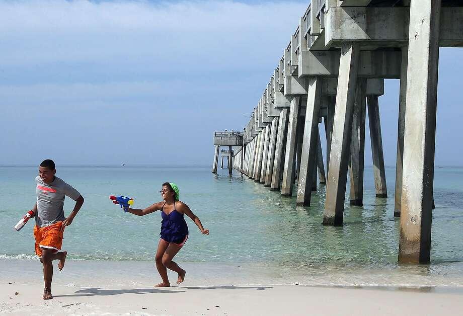 Halt or I'll moisten you!Maria Santana fires her water gun at a fleeing Jesus Martines in Panama   City Beach, Fla. Photo: Andrew Wardlow, Associated Press