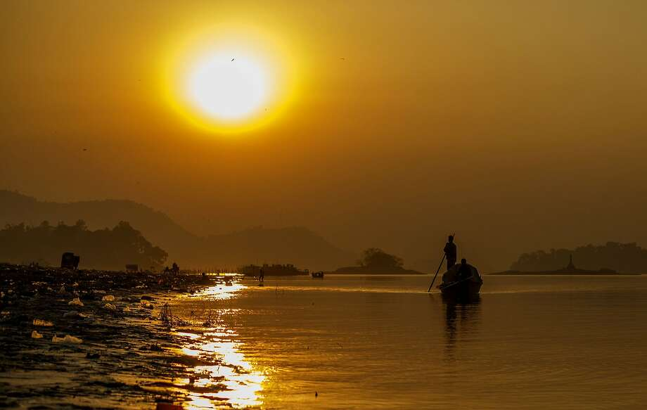 Indian boatmen paddle down the Brahmaputra River at sunset at Ujanbazar Ghat in Guwahati. Fishing 