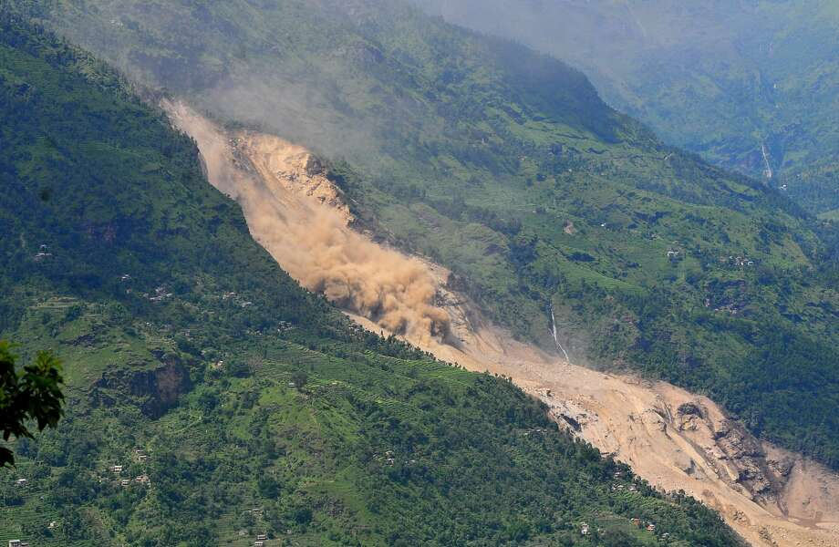 Loose earth slidesdown a slope, kicking up a cloud of dust, in the Sindhupalchowk area of Nepal. A 