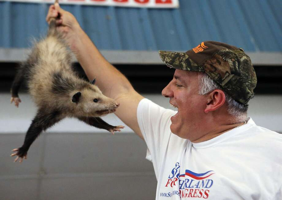 It's what I always wanted!U.S. Rep. Steve Southerland (R-Florida) grins as he wins an auctioned possum during the Wausau Possum Festival in Wausau, Fla. The possum doesn't share his enthusiasm. Photo: Heather Leiphart, Associated Press