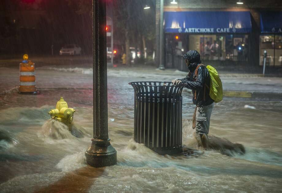 Monsoon season in the Southwest: A pedestrian hangs onto a trash can as rainwater flows towards downtown Albuquerque during a flash flood. Photo: Roberto E. Rosales, Associated Press