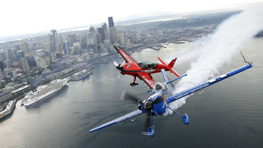 Daring ballet over Seattle: Pilots John Klatt, flying the blue Air National Guard MX-S airplane, and Jeff Boerboon in the red Jack's Links Extra 300L plane, fly in formation above Seattle during practice for the Boeing Seafair Air Show. Photo: Ted S. Warren, Associated Press