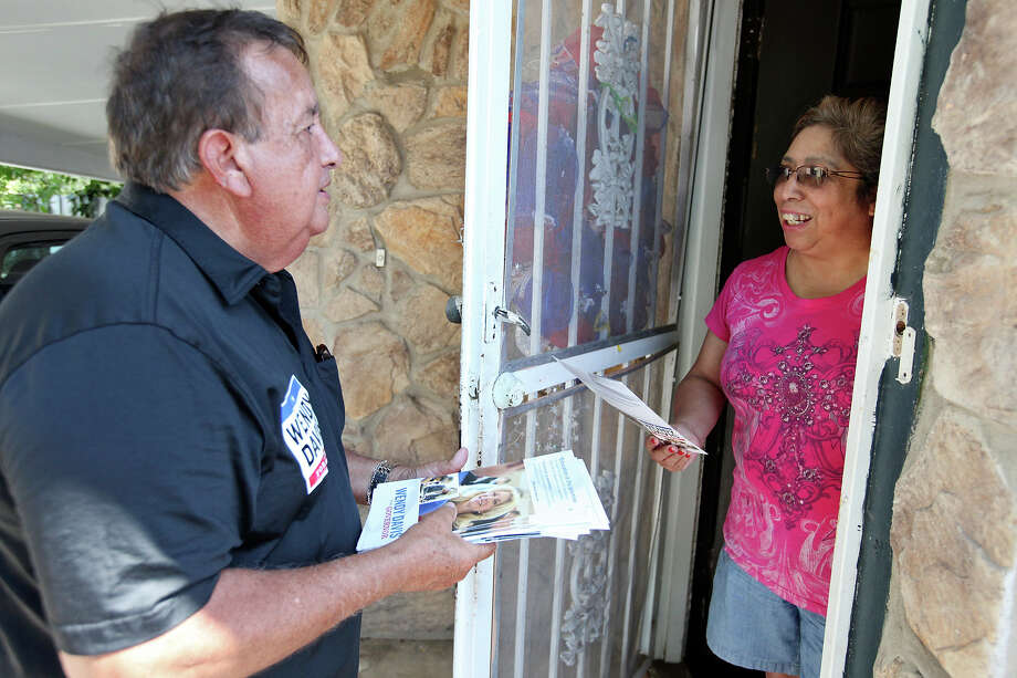 Wendy Davis campaign volunteer David Aguilar (left) talks with Sylvia Garza at her home during a block walk Saturday Aug. 2, 2014 on the city's Southeast side. Photo: Edward A. Ornelas, San Antonio Express-News / © 2014 San Antonio Express-News