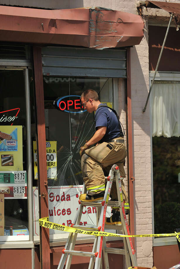 Stamford firefighter Chris Gloersen asseses the broken window at Viviano's Market on Hamilton Avenue in Stamford, Conn., on Monday, Aug. 4, 2014 after the driver of a tractor trailer allegedly backed into the convenience store as it was trying to turn around. One of the front windows was struck as well as a roll down security gate. Photo: Jason Rearick / Stamford Advocate