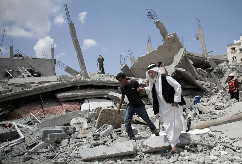 An elderly Palestinian man is helped while walking over rubble in a neighborhood in Gaza's Rafah area. Photo: Khalil Hamra, Associated Press