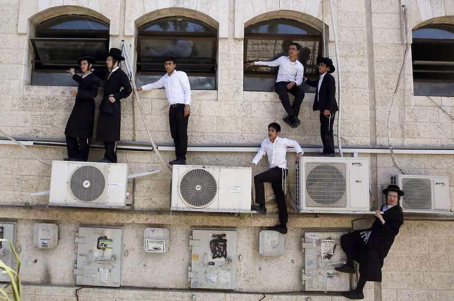 """TOPSHOTS Israeli ultra orthodox Jews watch as Israeli police work at the scene after a Palestinian man rammed an excavator into a bus, on August 4, 2014 in Jerusalem, killing one person and lightly injuring five others. The incident took place on the seamline between east and west Jerusalem and came as Israel pressed a major military campaign in Gaza which has killed more than 1,800 Palestinians. Police said the excavator had overturned a bus, prompting two police officers who were in the vicinity to open fire, killing the driver and foiling what they described as a """"terrorist attack"""".  AFP PHOTO / GALI TIBBONGALI TIBBON/AFP/Getty Images Photo: Gali Tibbon, AFP/Getty Images"""