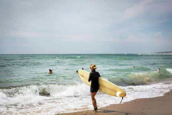 Joanna Nanci heads out into the water at the Ditch Plains beach near Montauk, N.Y., July 26, 2014. The recent closure for redevelopment of the East Deck Motel, a popular surfer haunt, is only the latest episode of gentrification in Montauk, which has long maintained a working-class atmosphere antithetical to the nearby Hamptons. (Jason Andrew/The New York Times)