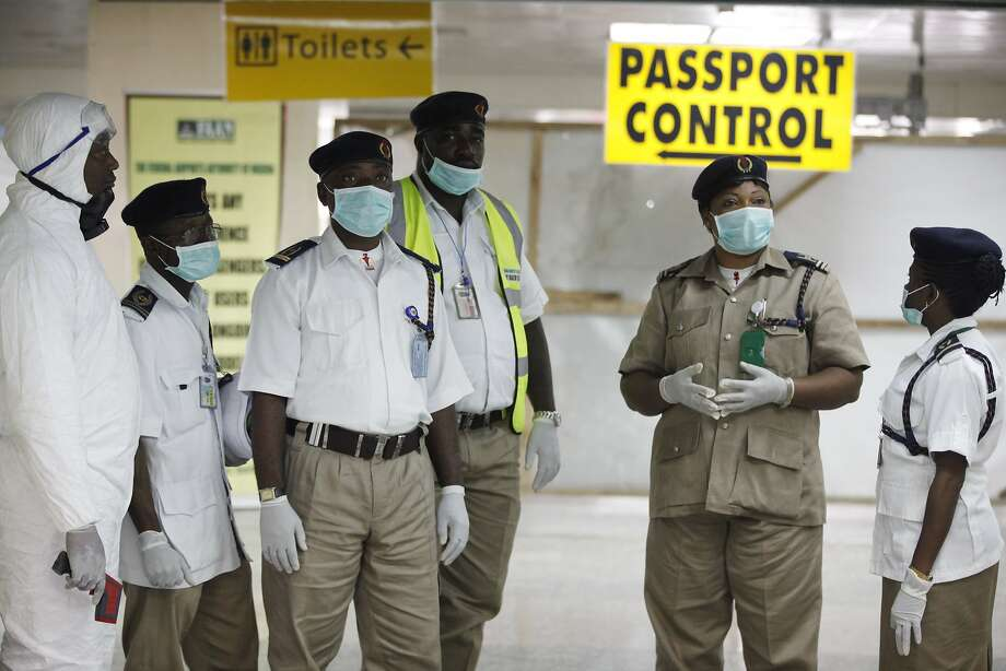 Nigeria health officials wait to screen passengers at the arrival hall of Murtala Muhammed International Airport in Lagos. Authorities have confirmed a second case of Ebola in Africa's most populous country. Photo: Sunday Alamba, Associated Press