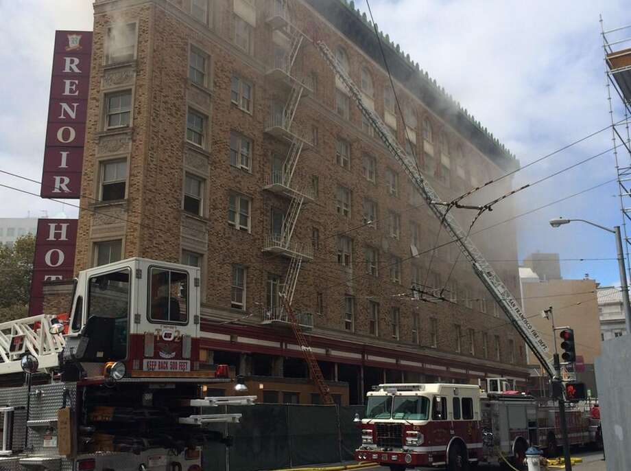Firefighters attack the blaze at Market and Mcallister from all sides of the old Renoir Hotel building, which looks to be boarded up. Photo: Kale Williams, The Chronicle