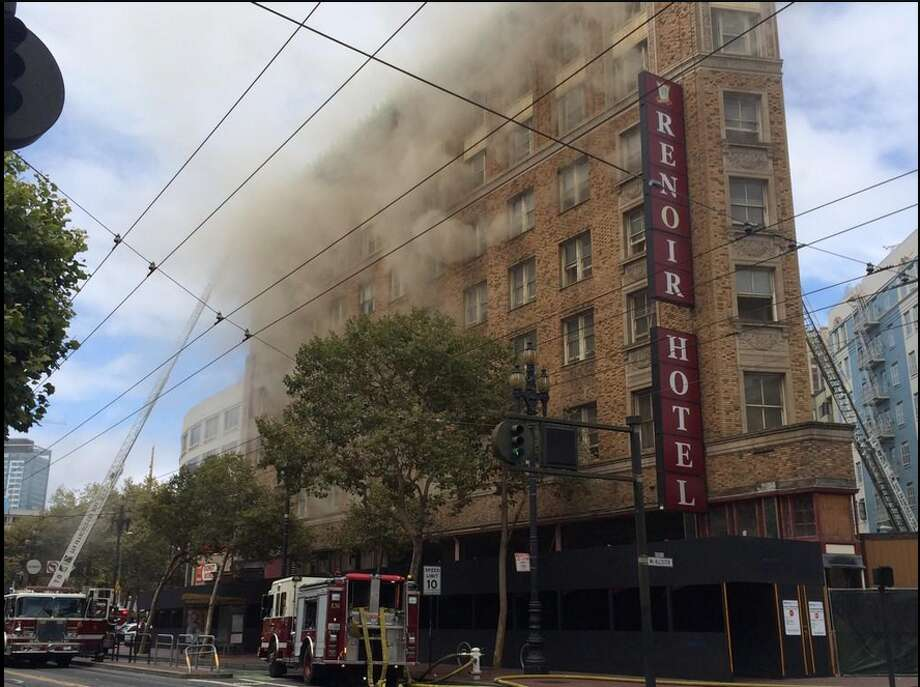 Smoke pours out of windows on all sides of the shuttered Renoir Hotel. Photo: Kale Williams, The Chronicle