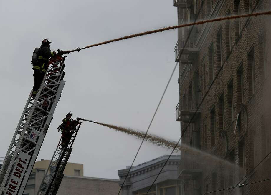 Two hoses were trained on the north side of the building Monday August 4, 2014. San Francisco firefighters battled a smokey fire at the shuttered Renoir Hotel on McAllister Street. Fire crews closed Market Street and adjoining avenues pouring water into the hotel. Photo: Brant Ward, San Francisco Chronicle