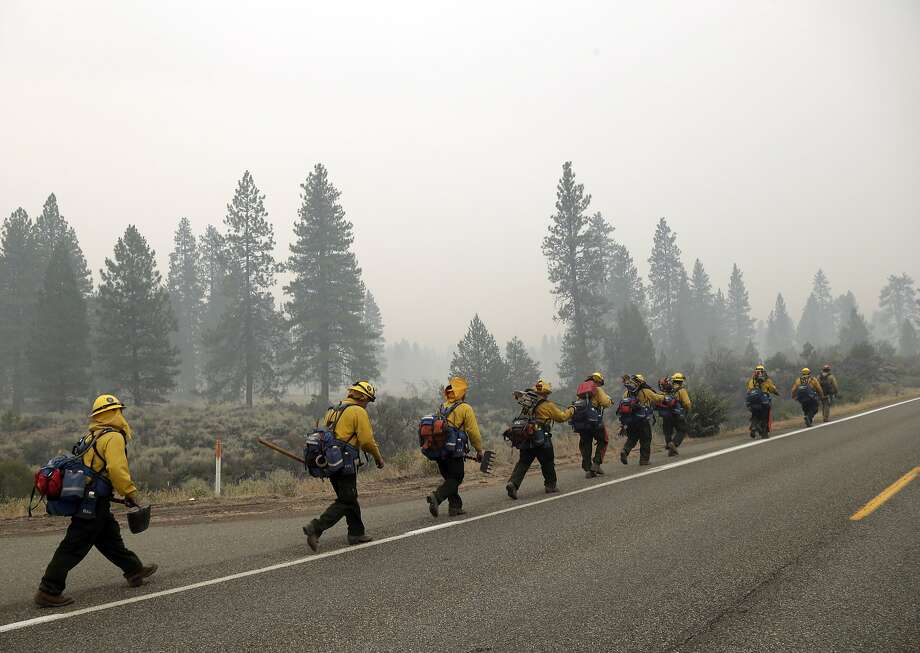 The Black Eagles 5 fire crew out of Porterville, Calif., walk along a road as smoke from the Eiler Fire fills the air on Monday, Aug. 4, 2014, in Hat Creek, Calif. Firefighters were focusing on two wildfires near each other in Northern California that have burned through more than 100 square miles of terrain. (AP Photo/Marcio Jose Sanchez) Photo: Marcio Jose Sanchez, Associated Press