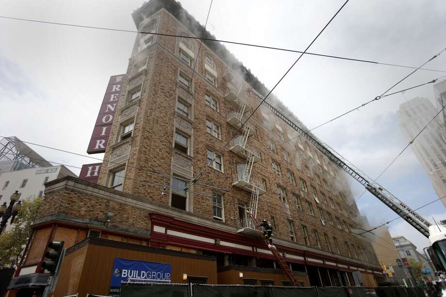 Smoke could be seen coming from the windows of hotel being renovated Monday August 4, 2014. San Francisco firefighters battled a smokey fire at the shuttered Renoir Hotel on McAllister Street. Fire crews closed Market Street and adjoining avenues pouring water into the hotel. Photo: Brant Ward, San Francisco Chronicle