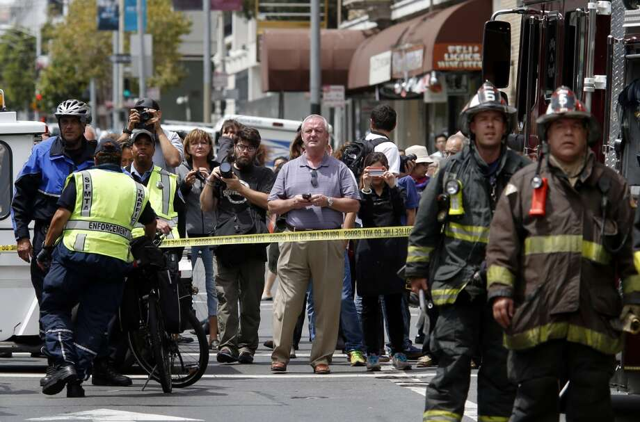 Spectators were kept back on McAllister Street as windows were being broken in the Renoir Monday August 4, 2014. San Francisco firefighters battled a smokey fire at the shuttered Renoir Hotel on McAllister Street. Fire crews closed Market Street and adjoining avenues pouring water into the hotel. Photo: San Francisco Chronicle