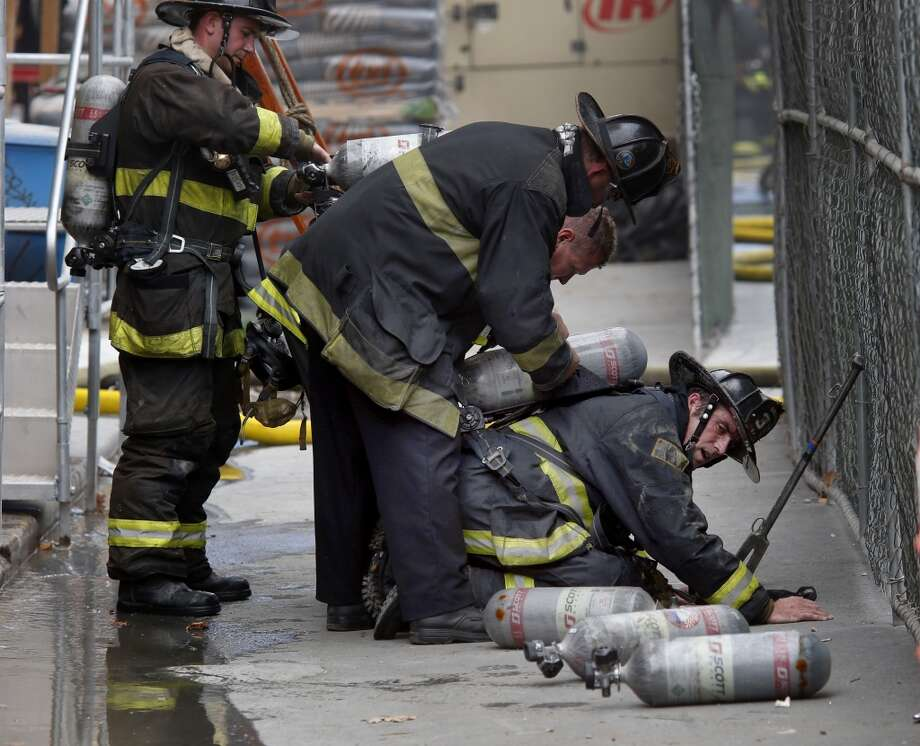 Fire fighters assisted a fireman with his oxygen tanks after exiting the burning building Monday August 4, 2014. San Francisco firefighters battled a smokey fire at the shuttered Renoir Hotel on McAllister Street. Fire crews closed Market Street and adjoining avenues pouring water into the hotel. Photo: San Francisco Chronicle
