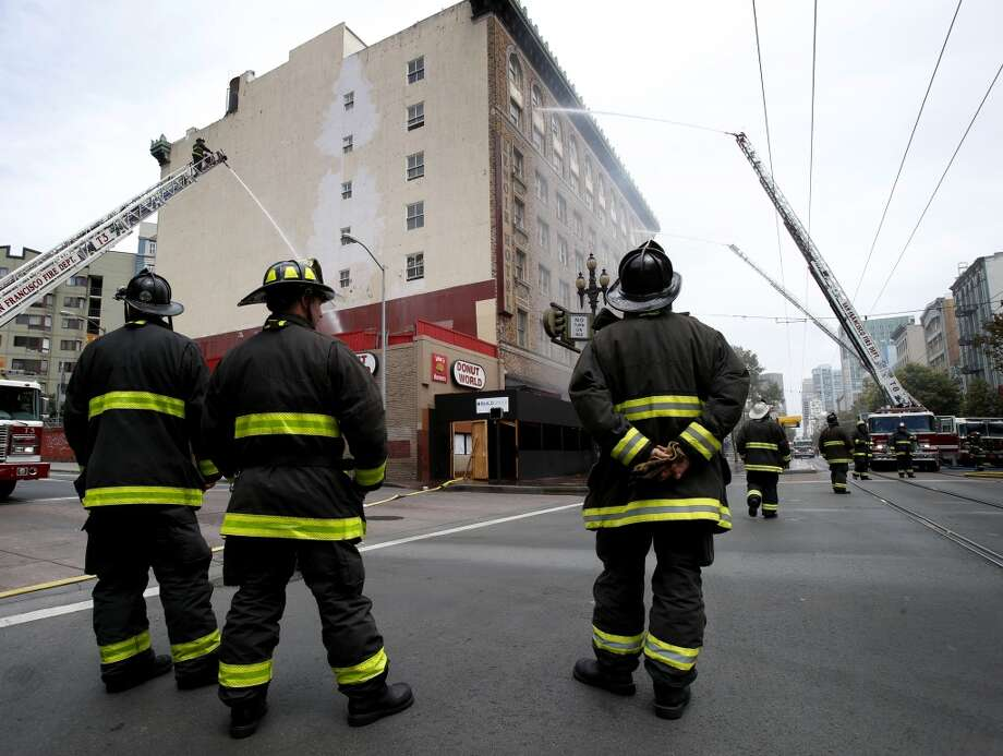 On Market Street, fire fighters fought the fire with two unmanned hoses and shut down the roadway Monday August 4, 4014. San Francisco firefighters battled a smokey fire at the shuttered Renoir Hotel on McAllister Street. Fire crews closed Market Street and adjoining avenues pouring water into the hotel. Photo: San Francisco Chronicle