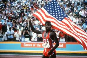 LOS ANGELES, UNITED STATES:  Carl Lewis from US holds the American flag after winning the 100m Men's final in 9:99, at the Los Angeles Olympic games, 04 August 1984. Four years later, at the Seoul 1988 olympic games, Lewis also took gold in the same category. (Photo credit should read AFP/AFP/Getty Images)