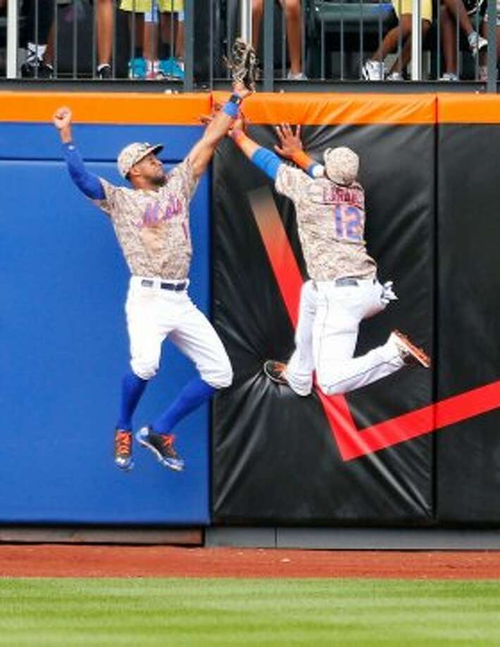 Chris Young of the New York Mets and teamate Juan Lagares (12) are unable to catch a triple off the bat of Hunter Pence. Photo: Mike Stobe, Getty Images
