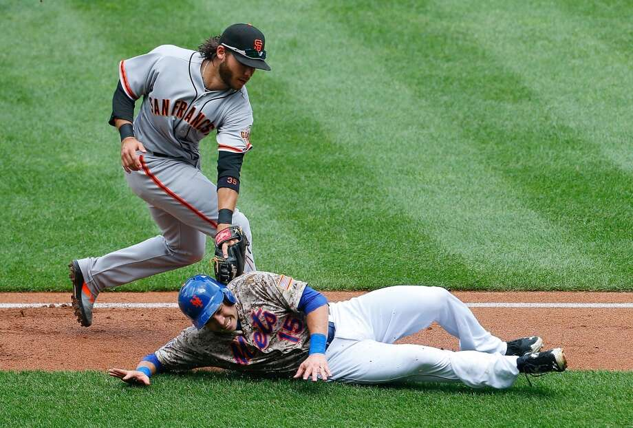 Travis d'Arnaud of the New York Mets is tagged out Brandon Crawford  of the San Francisco Giants during a run down in the fourth inning. Photo: Mike Stobe, Getty Images